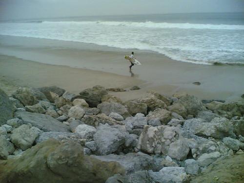 Surfista a ir para a água na praia do Cabedelo